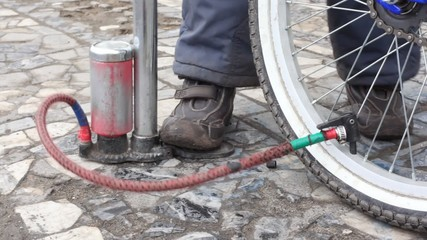 boy's foot on air-pump, pumping bicycle wheel