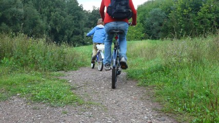 man and boy riding bicycles in park, from camera