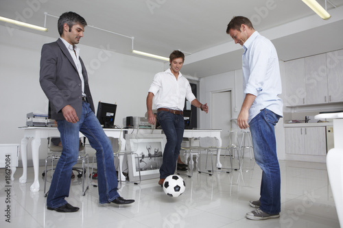 Young businessmen playing football