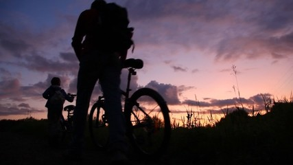 man and boy riding bicycles on sunset background