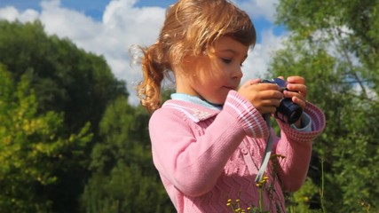 little girl with photo camera in park