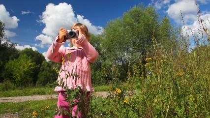 little girl photographs flower outdoor