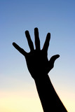 Silhouette of a hand against a sky