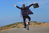 Carefree businessman holding a briefcase and riding a bicycle poster