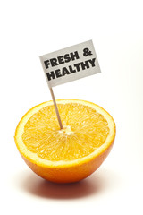 "sliced orange with flag ""fresh & healthy"" in front of white back"