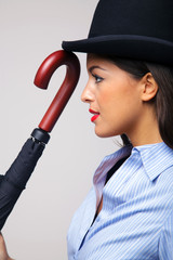 Businesswoman in bowler hat with umbrella.