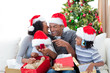 Happy Afro-American family having fun with Christmas presents