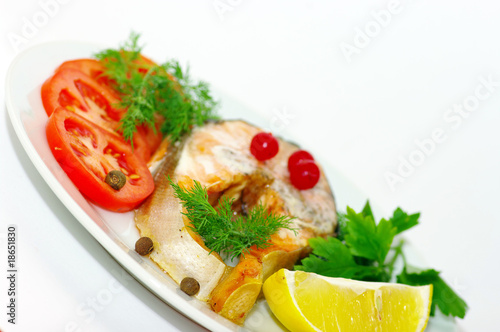 grilled fish with vegetables and spices on the white background