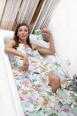 glücklich Frau sitzt in einer badewanne voller geld