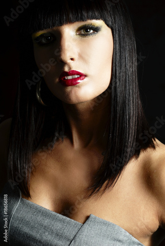 elegant brunette woman posing on dark background - close up