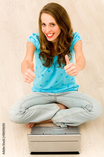 Girl with thumbs up using laptop