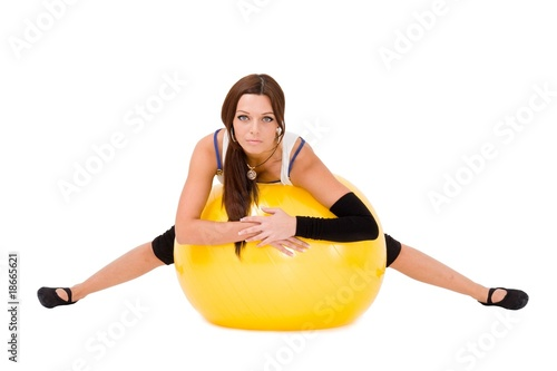 Attractive young woman on a fitness ball on white background