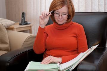 Redheaded schoolteacher marking homework