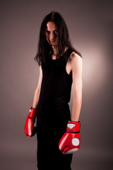 serious gothic emo man in boxing gloves isolated on gray
