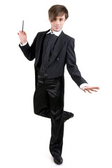 A young man in a black tailcoat is standing on one leg, isolated