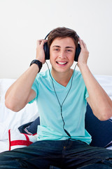 A teenage guy listening to the music in his bedroom