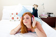Teenager listening to music on her bed