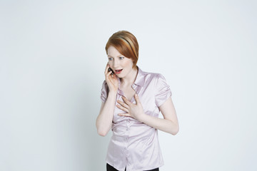Studio shot of woman talking on mobile phone