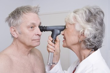Senior medical practitioner examines man for sight test