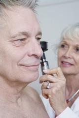 Senior medical practitioner examines man for hearing