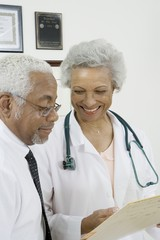 Senior healthcare professionals discuss medical records