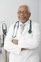 Senior healthcare professional stands with arms folded