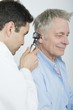 Mid adult doctor checks hearing of senior patient