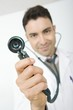 Mid adult doctor smiling and holding stethoscope