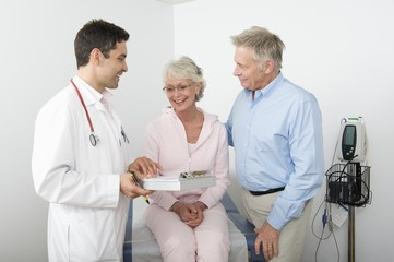 Mid adult doctor explains test results to senior couple