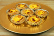 Portuguese egg tarts on golden plate