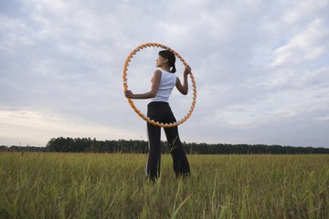 Mid adult woman stands with hula hoop in a field