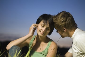 Couple sit listening to music on shared earphones