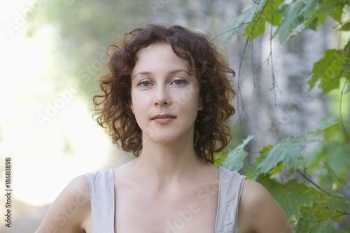Mid adult woman stands in nature looking directly at camera