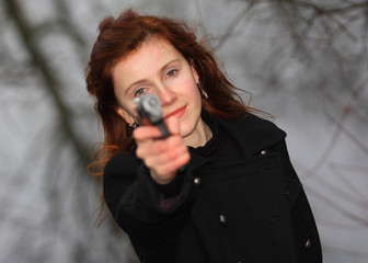 a pretty young woman aiming with the gun