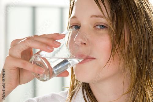 canvas print picture Frau im Bademantel trinkt ein Glas Wasser