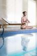 Woman meditating in lotus pose and meditating at poolside