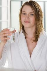 Frau im Bademantel trinkt ein Glas Wasser
