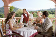 Waiter serving meals to well-dressed couples at table on restaurant balcony