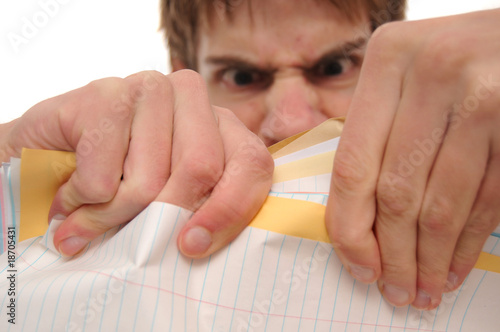 Angry young man ripping papers