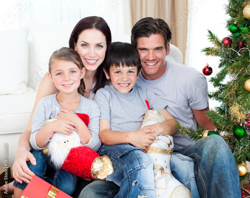 Portrait of a smiling family at Christmas time holding lots of p