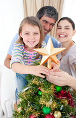 Father lifting his daughter to put the Christmas star on top of