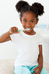 Portrait of a smiling little girl brushing her teeth