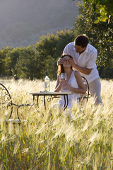 Man surprising woman drinking white wine at table in rural field