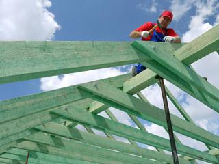 Carpenter driving a nail into house rafter framing beam