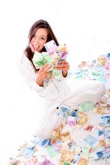 Glückliche Frau sitzt auf vielen Geldscheinen und hält einige in