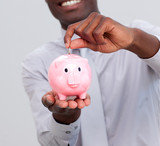 Afro-American businessman saving money in a piggybank