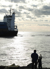 Silhouettes of father and son looking at ships in the see