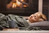 Fototapety Woman sleeping beside fireplace