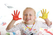 Closeup of a smiling child with painted hands making grimace