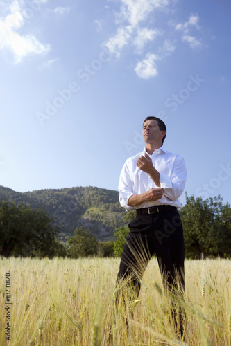 Businessman rolling up sleeves in rural field